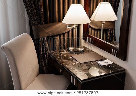 Interior Hotel Apartment, Comfortable Room, Mirror And Desk. Folder For Notes And Lamp Standing On A