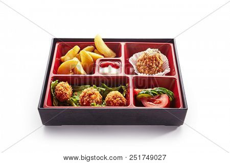 Asian Style Lunch Box with Deep Fried Balls, Salad, French Fries and Dessert. Fresh Food Portion in Bento Box with Vegetables, Baked Potatoes, Meat in Breadcrumbs and Cake Isolated on White