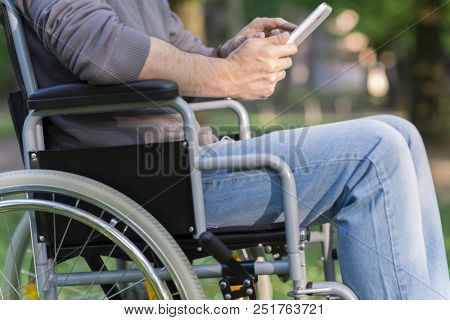Detail of a disabled man using a tablet in a park