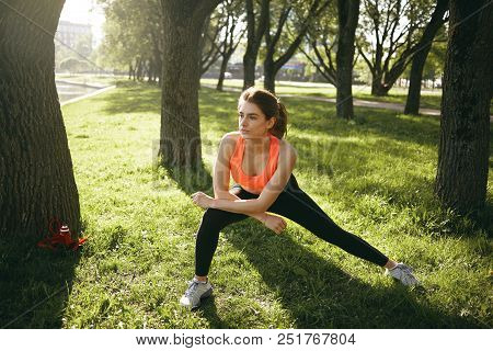 Attractive Confident Young Sportswoman With Pony Tail Warming Up, Stretching Before Running Routine,