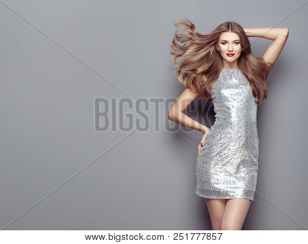 Fashion Portrait Young Woman In Elegant Silver Dress. Girl With Elegant Hairstyle Posing On A Gray B