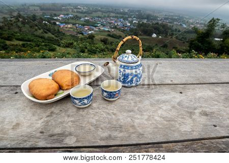 Tea Pot With Cup Set And Fried Steamed Bun On The Wooden Table In Front Of Mountain View, Traveling