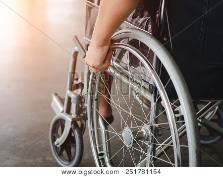 A Disabled Man Is Sitting In A Wheelchair. He Holds His Hands On The Wheel. Handicap People Concept.