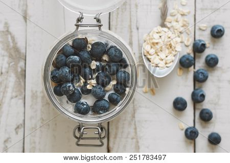 Overnight oats with soaked in coconut milk with fresh bluberry on wooden table, top view. Healthy breakfast poster