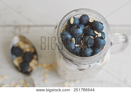 Overnight Oats With Blueberry On Wooden Table. Homemade Yogurt With Whole Grain Oats. Healthy Breakf