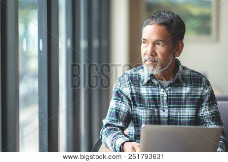 Mature Man With White Stylish Short Beard Looking Outside Window. Casual Lifestyle Of Retired Hispan