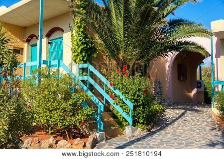 Greek Yellow House With Blue Wood Elements And Plants On The Front Yard