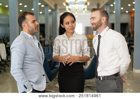Three Positive Business People Chatting In Office. Businesspeople Standing With Blurred Office Inter
