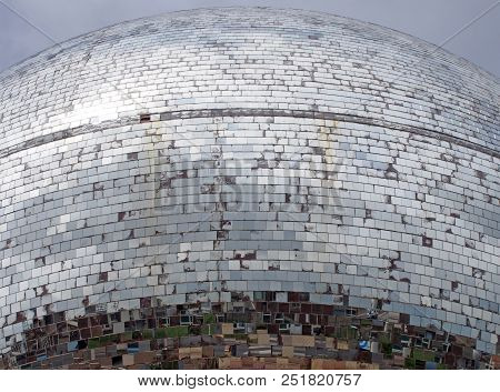 an outdoor mirror ball made of thousands of pieces of glass reflecting a grey cloudy sky and fragmented images of an urban street in blackpool poster