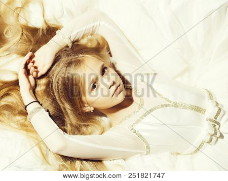 small girl kid with long blonde hair and pretty serious face in prom dress lying on white fabric, closeup poster