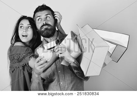 Man With Beard Holds Credit Card And Piggy Bank. Couple Holds Shopping Bags And Hug On Pink Backgrou