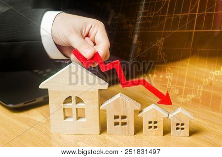 The Hand Holds A Red Arrow Above The Wooden Houses Down. The Houses Are Decreasing. The Concept Of F