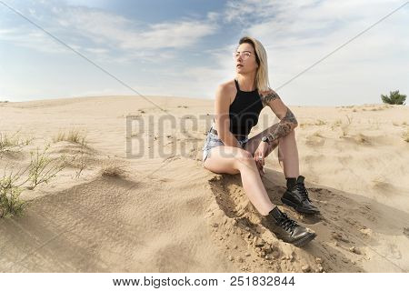 Portrait Of A Woman In Shorts Sitting On The Sand In The Desert And Looking Sideways