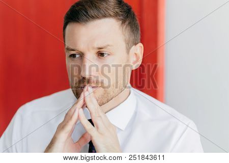 Thoughtful Attractive Male Keeps Hands Together Near Mouth, Has Pensive Expression, Dressed In White