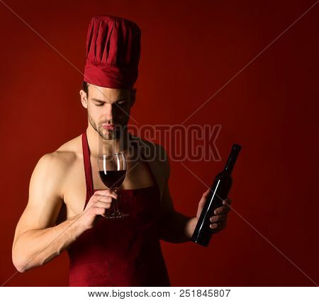 Restaurant. Wine Cellar. Chef In Apron Tastes Wine. Bearded Man Holds Bottle Wine. Silhouette Of Mal