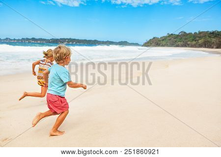 Happy Barefoot Kids Have Fun On Beach Walk. Run And Jump By White Sand Along Sea Surf. Family Travel