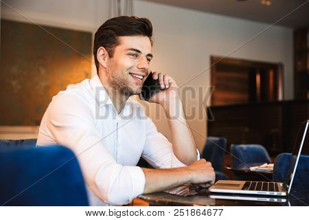 Portrait of a smiling young formal dressed man talking on mobile phone working on laptop computer while sitting at the hotel lobby