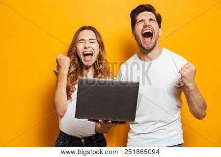 Portrait of ecstatic man and woman shouting and clenching fists like winners or happy people while holding black laptop isolated over yellow background
