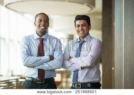 Cheerful Ambitious Coworkers Standing With Arms Folded. Successful Confident Business People Smiling
