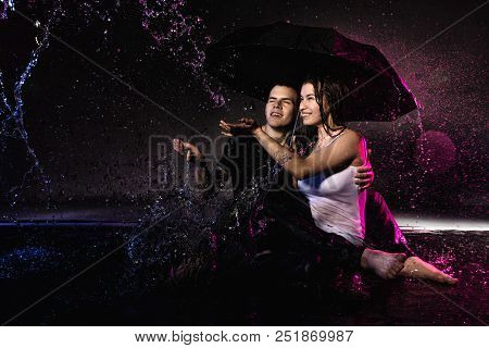 Couple Young Teens Together In Small Pool, Drops Of Water And Colored Light Behing Them
