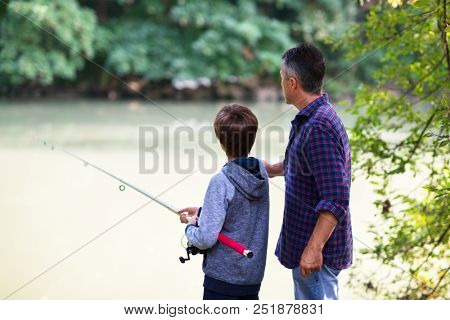 Father with son fishing at river bank, summer outdoor. Man and young boy standing at river bank with rod and fishing. Family leisure, parenting. Fishing. Angling.