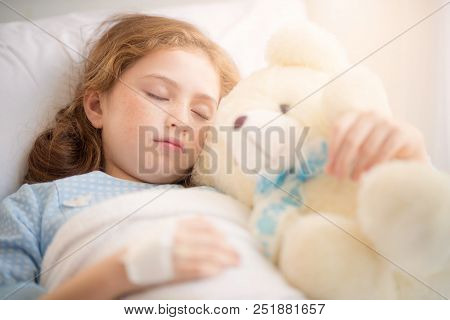 Adorable Little Girl Resting In A Hospital Bed With Her Teddy Bear. Selective Focus At Her Left Eye.