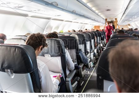 Interior Of Commercial Airplane With Unrecognizable Passengers On Their Seats During Flight. Steward
