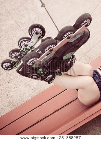 Woman wearing roller skates sitting on bench with raised legs. Bizarre high angle poster