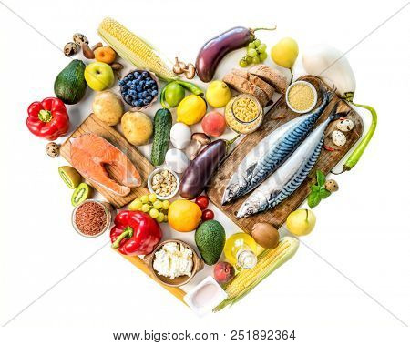 Healthy organic nutritious diet. Plenty of foods on the wooden white table in the form of the heart