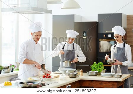Busy chef and his cooks working at kitchen and cooking pasta at counter: chef cutting tomatoes, young man in apron checking spaghetti, serious lady whipping ingredients