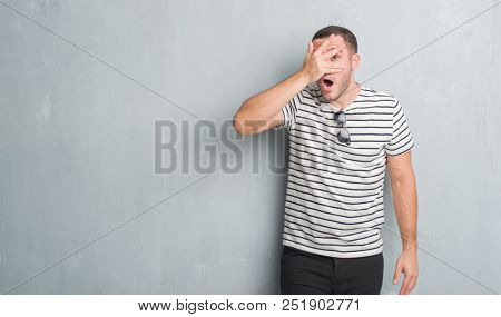 Young caucasian man over grey grunge wall peeking in shock covering face and eyes with hand, looking through fingers with embarrassed expression. poster