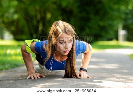 Fitness And Healthy Lifestyle Concept - Cute Girl Doing Push-up Exercise On The Park In A Sunny Morn