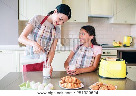 Eautiful Woman Is Pouring In Milk To Glass Cups. Girl Holds Her Own Cup And Looks At Mom. She Smiles