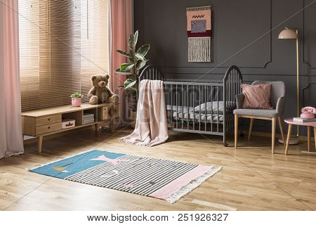 Real Photo Of A Baby Crib Standing Between A Low Cupboard And An Armchair, Lamp And Stool In Child's