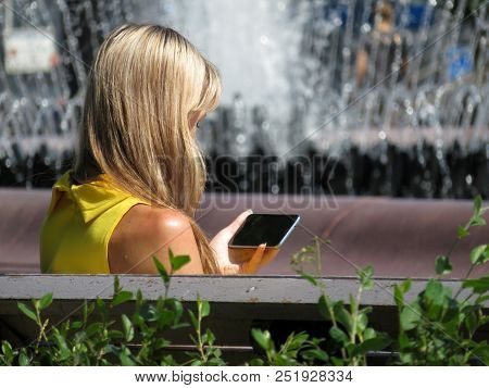 Blonde Girl Sitting With A Smartphone In Her Hand Against The Summer Fountain. Concept For Text Mess