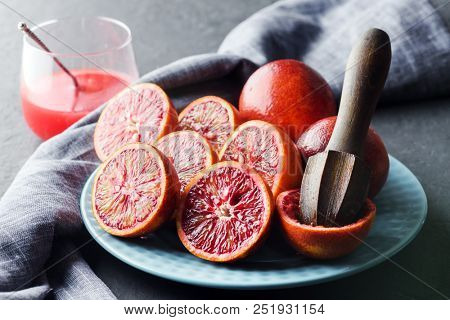 Red sicilian orange pieces and wooden squeezer on blue plate closeup. Healthy diet vitamin concept. Food photography