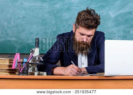 School Paperwork. Paperwork Part Of Teachers Life. Teacher Sit Desk With Laptop. Teacher Bearded Hip