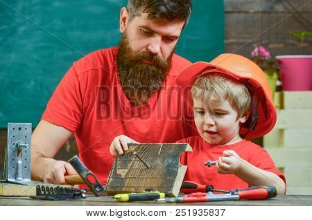 Father, parent with beard teaching little son to use hobnails and hammer. Masculine duties concept. Boy, child busy in protective helmet learning to hammering hobnails with dad. poster