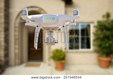 Back of Unmanned Aircraft System (UAV) Quadcopter Drone Flying In Front of House. poster