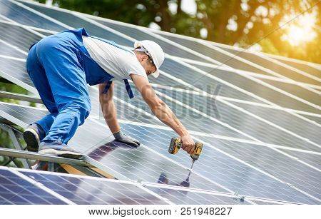 Construction Worker Connecting Photo Voltaic Panel To Solar System Using Screwdriver On Shiny Surfac
