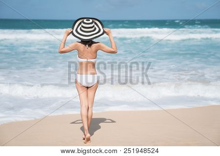 Back Of Young Woman In Bikini Standing On The Beach, Young Beautiful Sexy Woman In Bikini Swimsuit,
