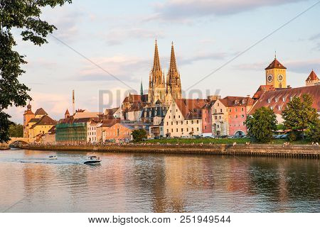 Regensburg City View, Germany. People Enjoy Beauty On Danube River Shore, Regensburg Cathedral And S