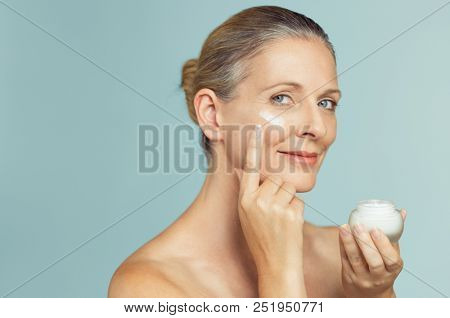 Beautiful mature woman holding jar of skin cream for face isolated on light blue background. Happy senior woman applying anti-aging moisturizer and looking at camera. Beauty and anti aging treatment.