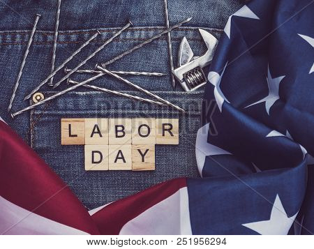 Usa Flag, Tools, And Wooden Letters With The Inscription Labor Day On The Background Of A Blue Jeans