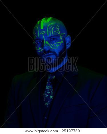 A caucasian male model with green blacklight paint. Paint resembles a circuit board. Dark suit with green accents poster