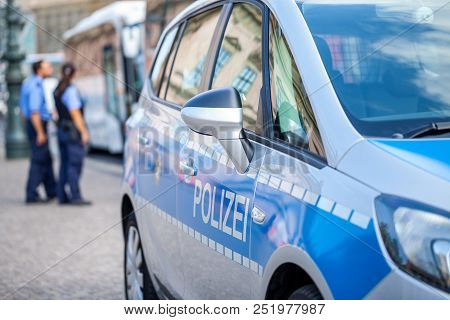 German Police Car Stands On Street. Two Police Officers Controls Traffic. Polizei Is The German Word
