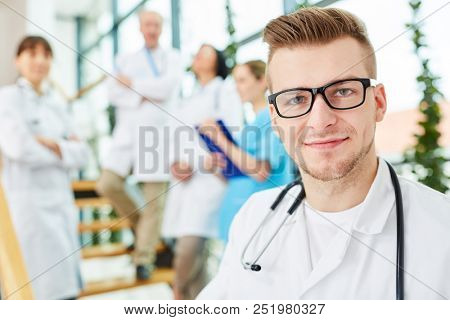 Young physician in medicine apprenticeship with team of doctors