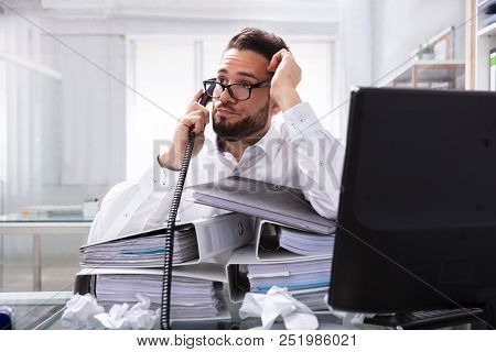 Overworked Businessman Talking On Landline With Stack Of Folders On Desk