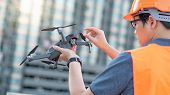 Young Asian engineer holding drone at construction site. Using unmanned aerial vehicle (UAV) for land and building site survey in civil engineering project. poster