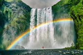 Iceland waterfall travel nature famous tourist destination. Skogafoss waterfall with rainbow and woman under water fall in magical landscape popular Europe attraction. t-shirt